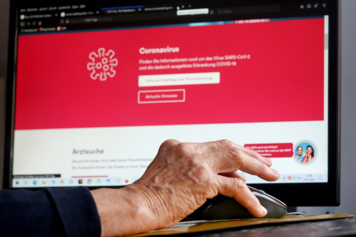 A retiree's hand on a mouse, in front of a desktop screen showing a website about coronavirus vaccination appointments.