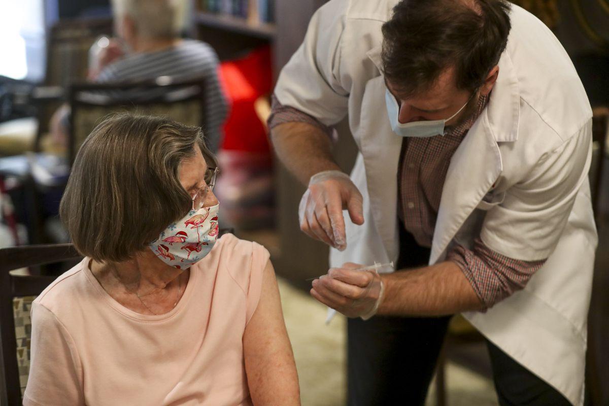 Pat Burton gets a COVID-19 vaccine from Walgreens pharmacist in Sandy, Utah.