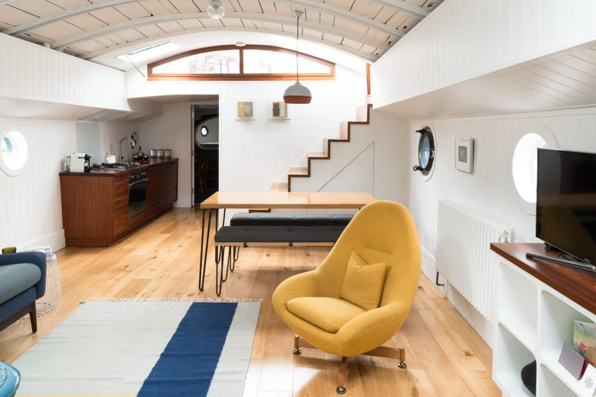 Interior of arched living space with white paneled walls and ceiling, hardwood floors, and built-in shelving.