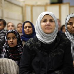 Muslim women and children attend a vigil and prayer service held to honor the victims of Wednesday's shooting rampage at the Chino Valley Islamic Center Friday, Dec. 4, 2015, in Chino, Calif. The FBI said Friday it is officially investigating the mass shooting in California as an act of terrorism, while a U.S. law enforcement official said the woman who carried out the attack with her husband had pledged allegiance to the Islamic State group and its leader on Facebook.