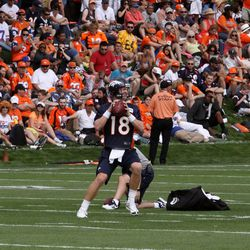 Peyton Manning throws as the crowd looks on