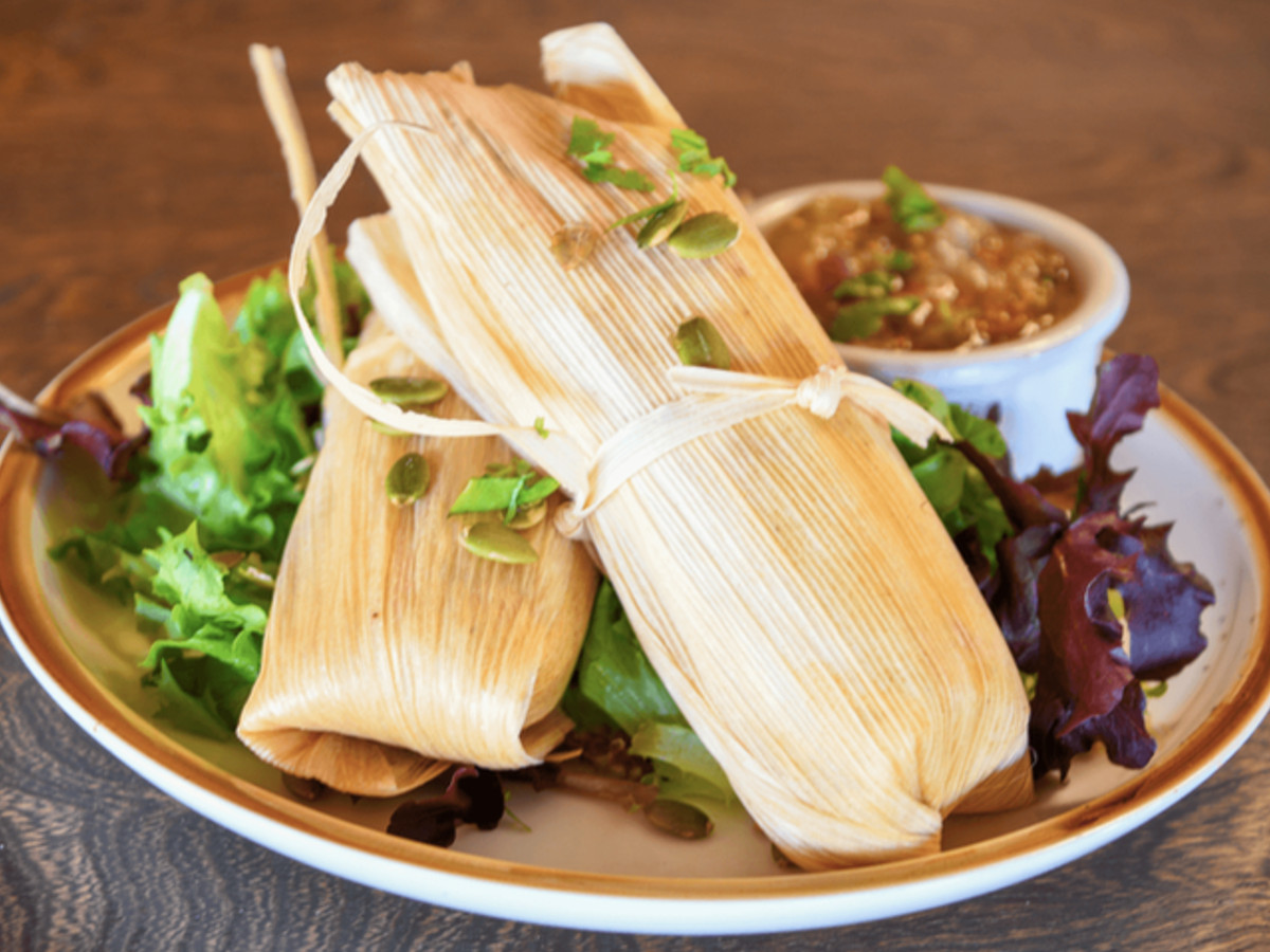 Two tamales wrapped in corn husks