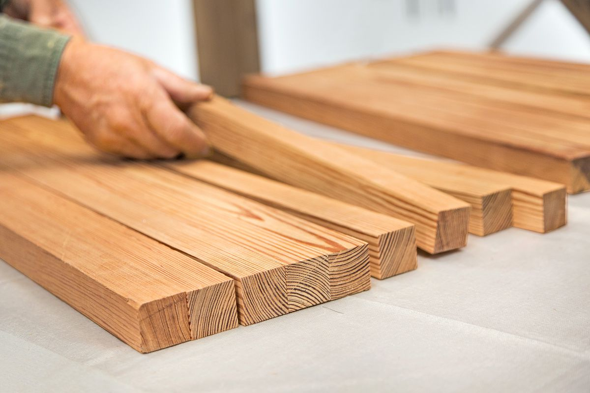 Cut strips of wood are laid out along the table, a person turns the strips so that each strip has a different pattern facing upwards.