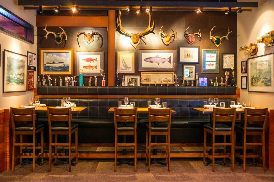 A wood bar with tall bar chairs and antler decor in the background