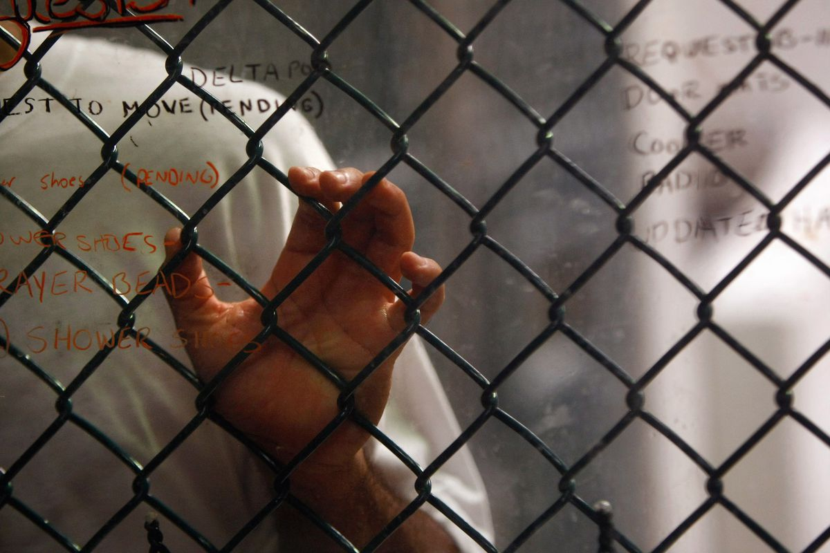 A Guantanamo detainee stands at the fence in 2009.