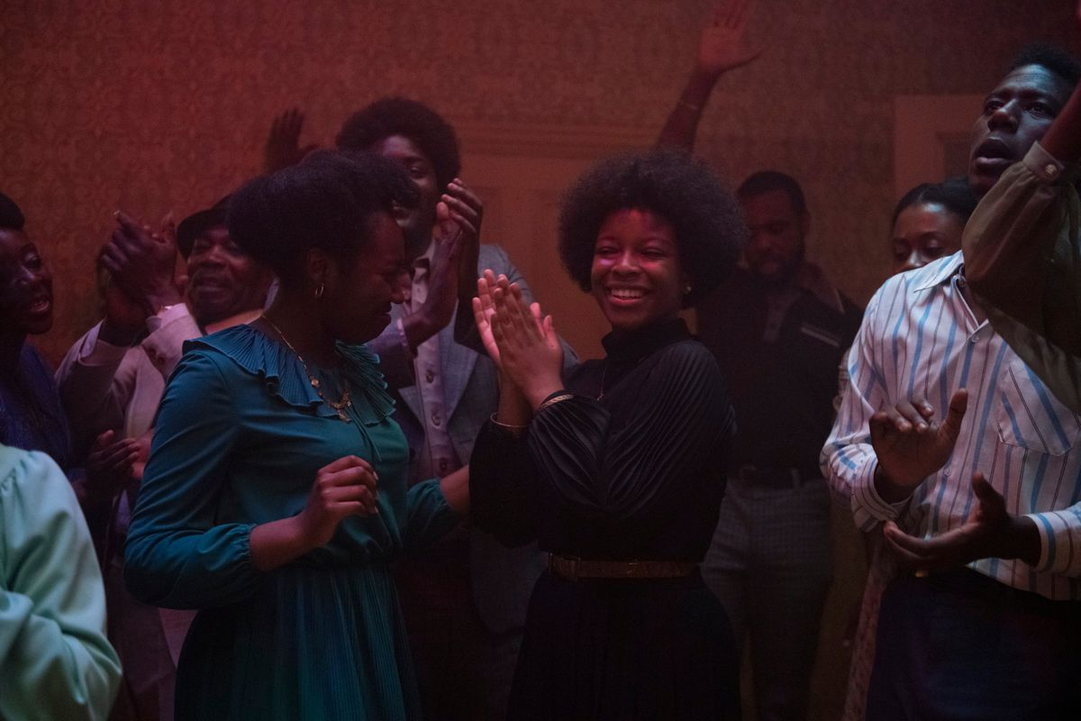 young black women and men dance at a house party in lovers rock