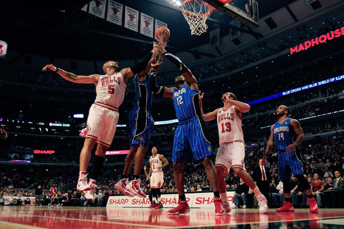 Carlos Boozer of the Chicago Bulls battles for a rebound with Rashard Lewis and Dwight Howard of the Orlando Magic while Joakin Noah sets up at the United Center on December 1 2010 in Chicago Illinois. (Photo by Jonathan Daniel/Getty Images)