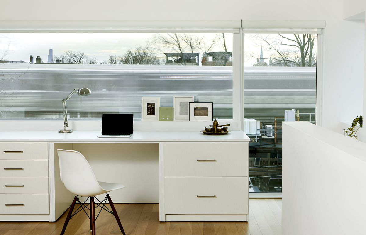 A white desk and chair are positioned in front of a window. Through the window, you can see a train whizzing by.