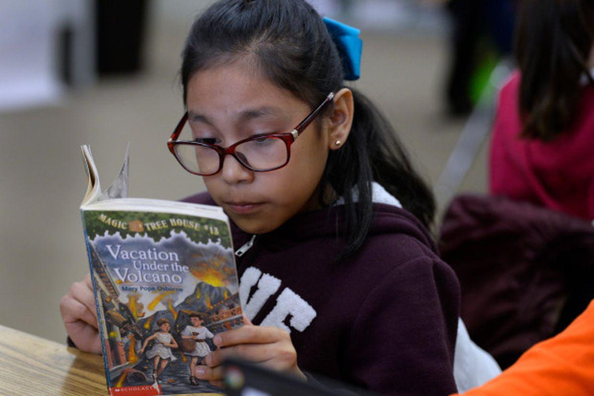 """A 10-year-old girl wearing glasses reads """"Vacation Under the Volcano"""" at a desk."""