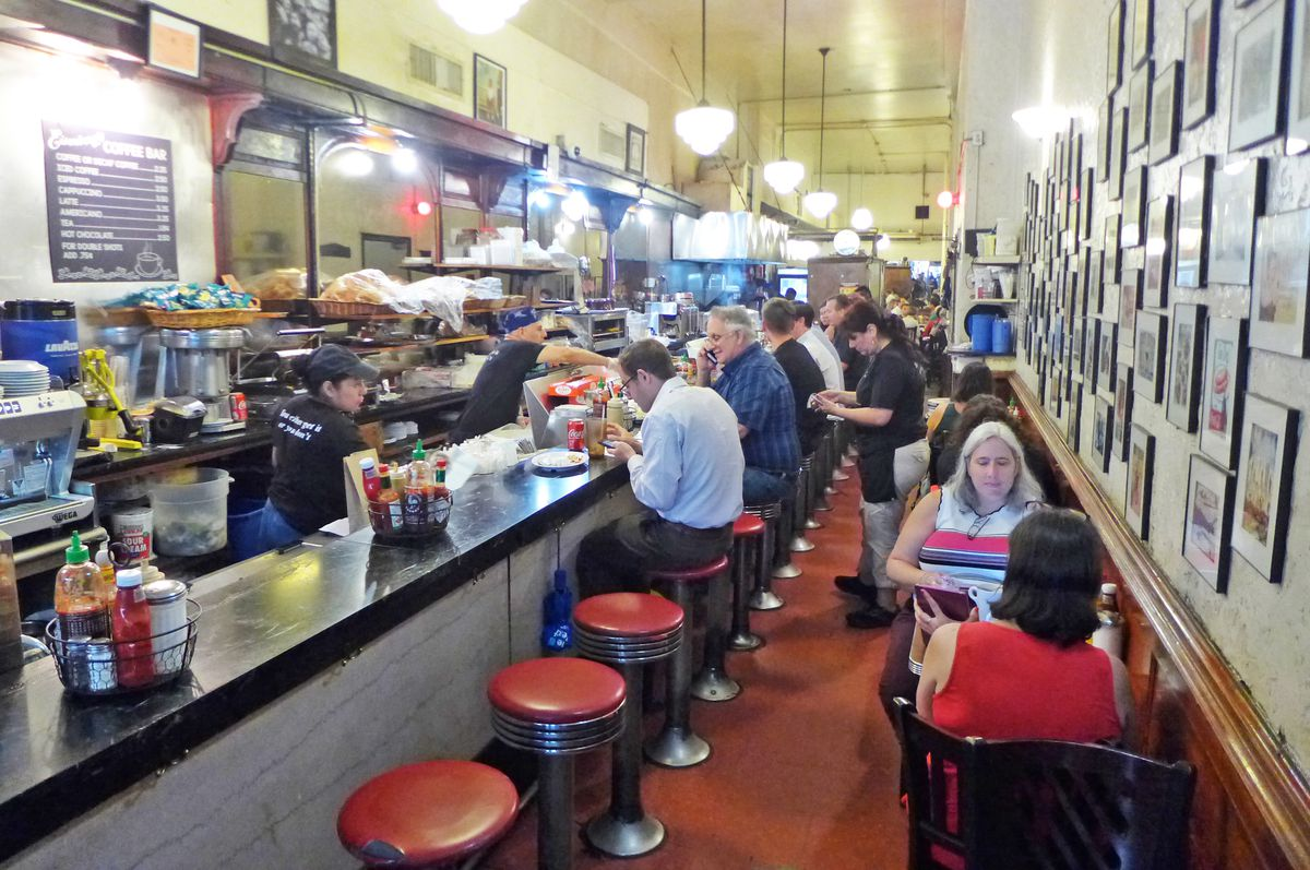 The interior of Eisenberg's is long and narrow, with an open kitchen, red stools, and tables on the side, filled with patrons.