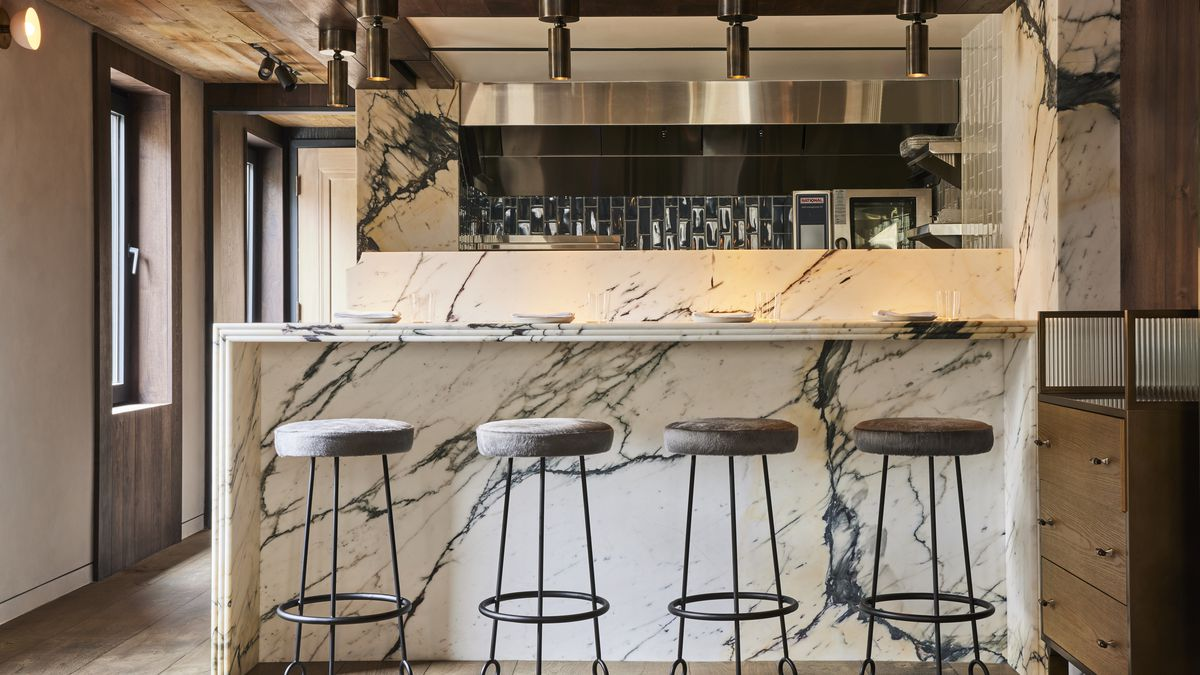 Four bar stools are pulled up to a granite countertop in the dining room of a restaurant