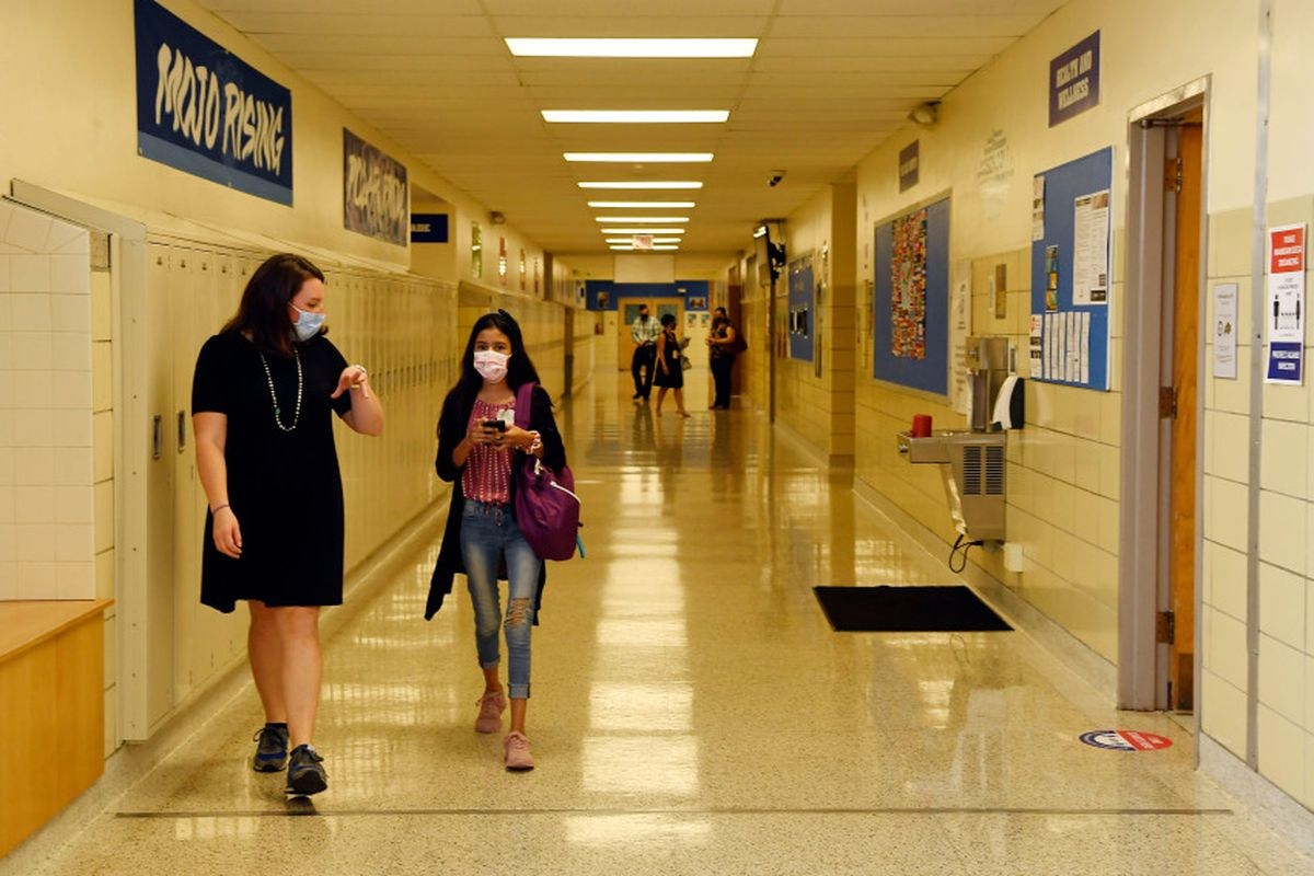 A teacher walks next to a student in a middle school hallway.
