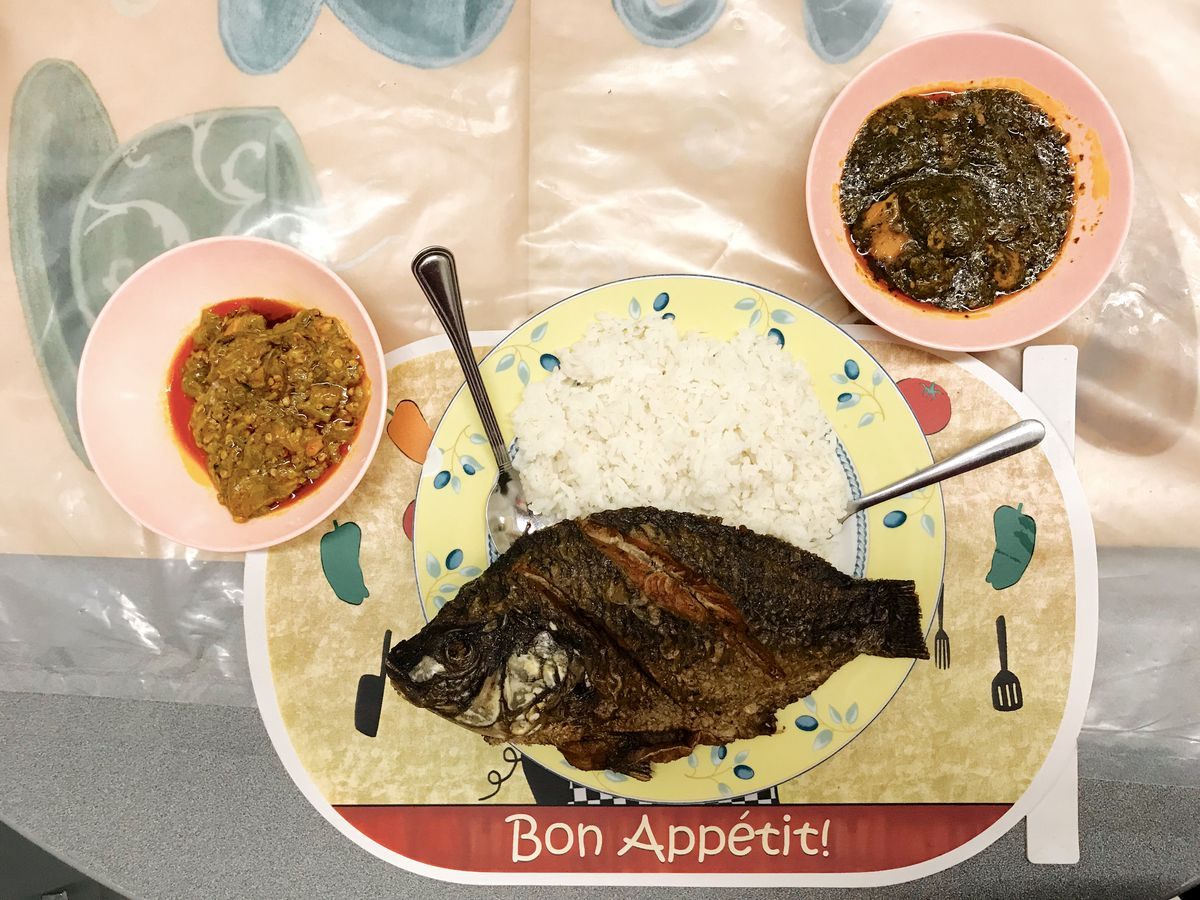 """A whole fried tilapia sits on a plate on a pile of white rice. Underneath is a placemat that reads """"Bon Appetit!"""" Two pink bowls hold side dishes."""