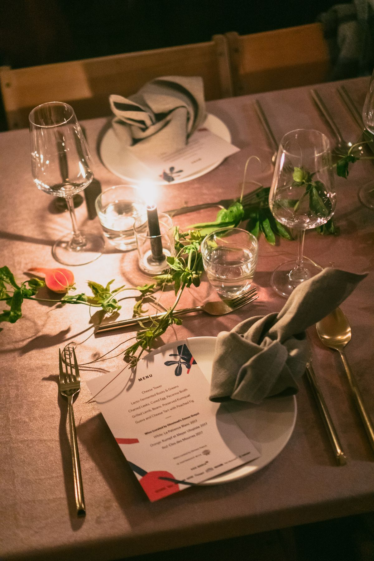 Candle-lit table with a menu sitting on a plate