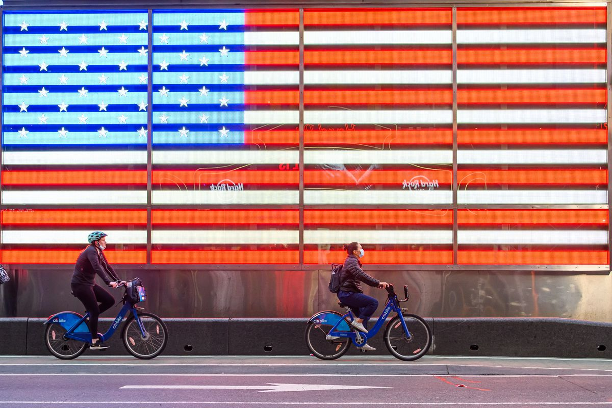 People ride bicycles past the US flag art installation in Times Square in New York City during the pandemic on May 7, 2020.
