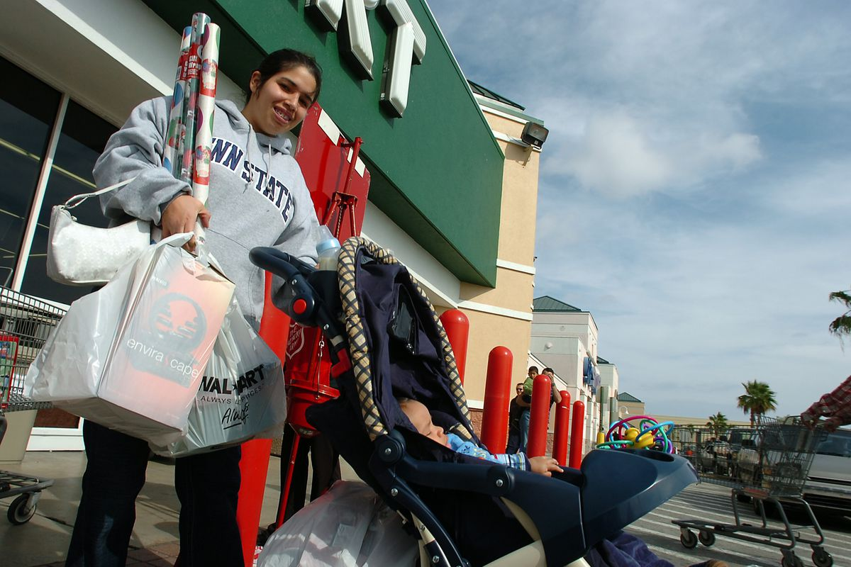 Michelle Espinosa-Clark and her 4-month-old son Jusue Clark of Miami, prepare for the holidays as they leave Wal-Mart with toys and gift wrapping paper Saturday, Dec. 9, 2006, in Miami.