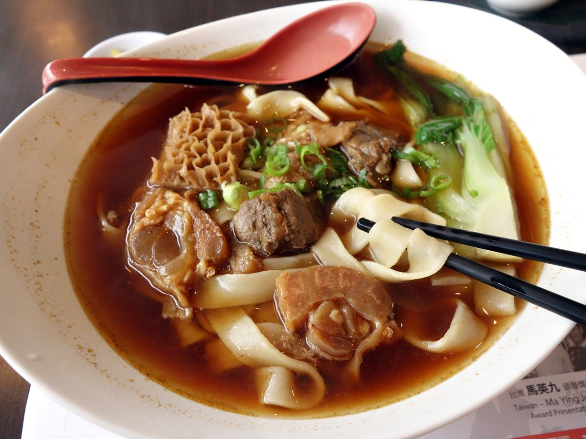 From above, chopsticks grab a few noodles from a soup also containing large hunks of tripe and beef shank, bok choy, diced scallions and broth, with a soup spoon resting on the far side of the bowl