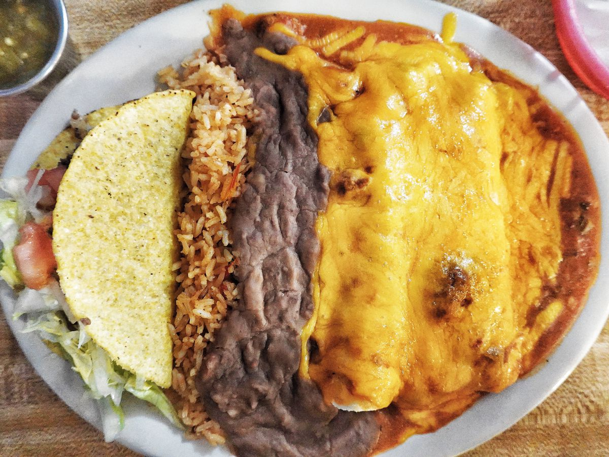 A white oval plate with a crispy taco, refried beans, and enchiladas covered in yellow cheese sauce.