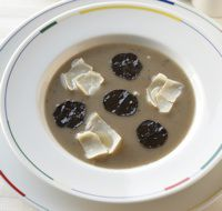 A bowl with a gray soup with truffles on top