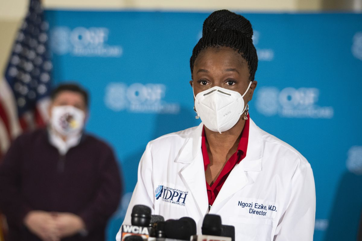 Gov. J.B. Pritzker looks on as Dr. Ngozi Ezike, director of the Illinois Department of Public Health, speaks to reporters after a nurse administered Illinois' first five Pfizer-BioNTech COVID-19 vaccinations outside of Chicago at OSF Saint Francis Medical Center in downstate Peoria.
