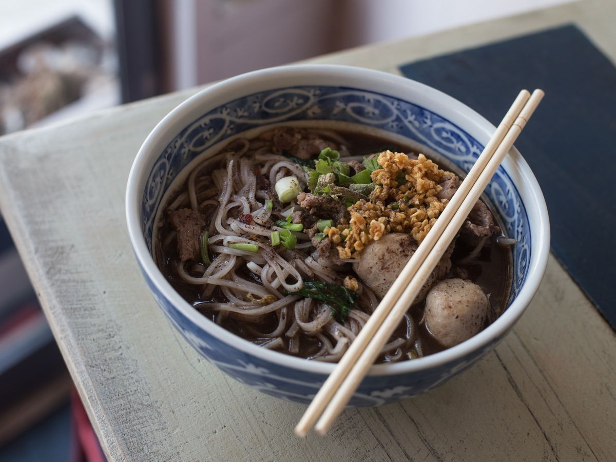 A bowl of noodles with chopsticks over it.