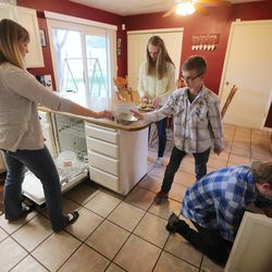 Becky Evans hands a bowl to her son Isaac as they all put dishes away Monday, May 11, 2015, as they spend time together at home in Murray.