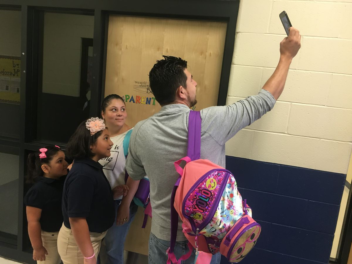 A family marks the first day of school with a selfie at Southwest Detroit Community School.