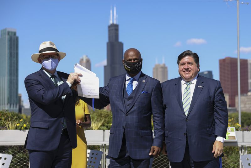 State Senate President Don Harmon, left, joins House Speaker Chris Welch, center, and Gov. J.B Pritzker after the governor signed the Climate and Equitable Jobs at Shedd Aquarium on Wednesday.
