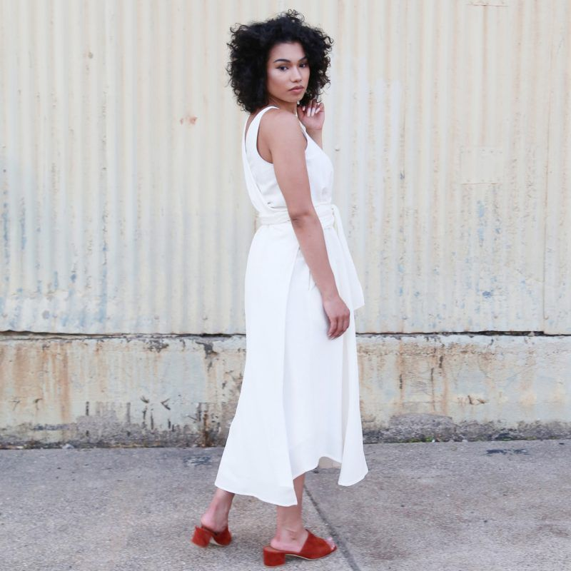 A model in a white wrap dress with red slides