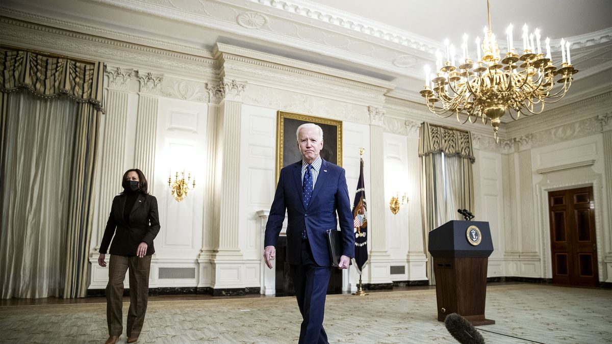 President Joe Biden walks away from the lectern in the State Dining Room of the White House, with Vice President Kamala Harris following to his right.
