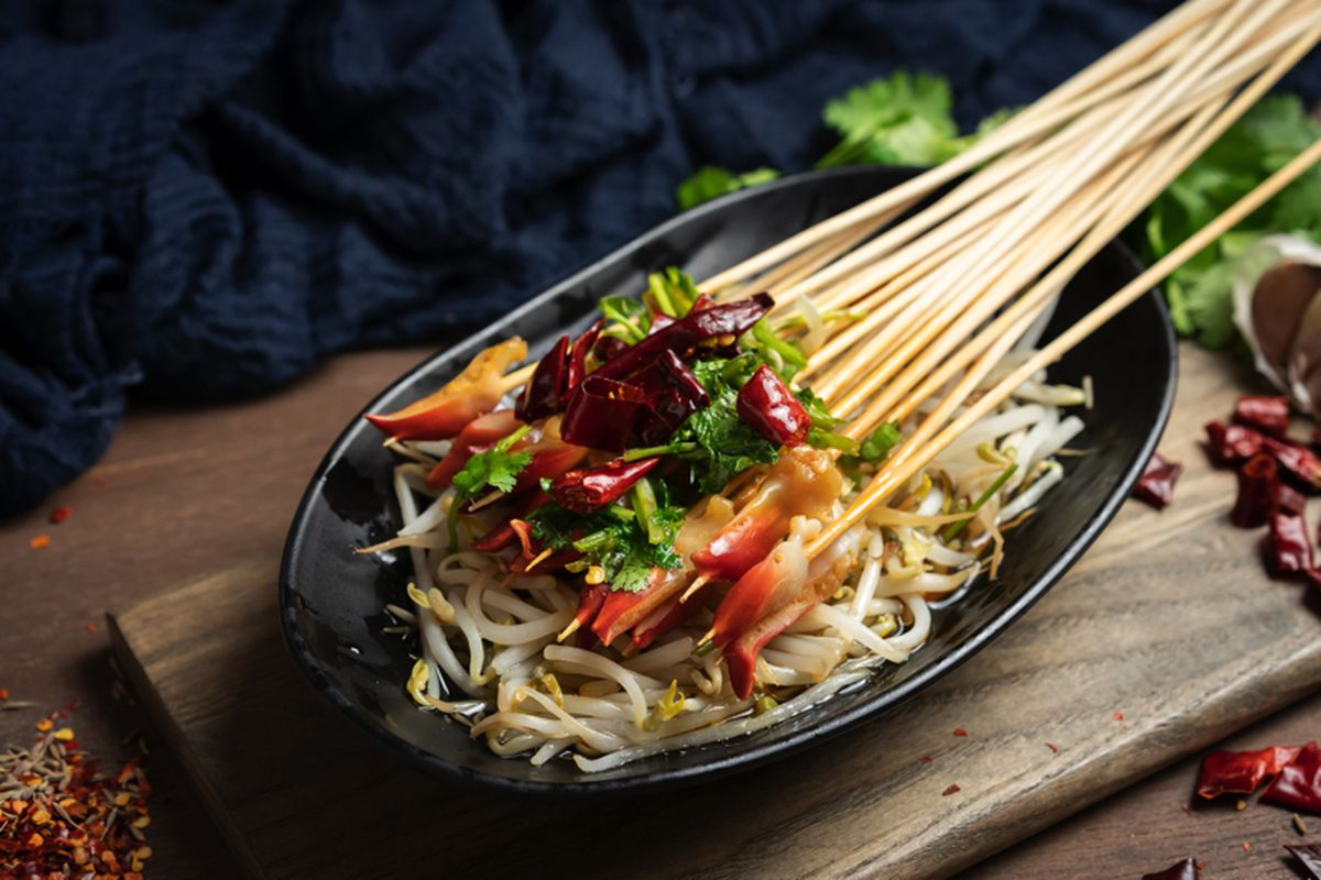 Chinese skewers with a variety of toppings over a bed of noodles on a wooden board.