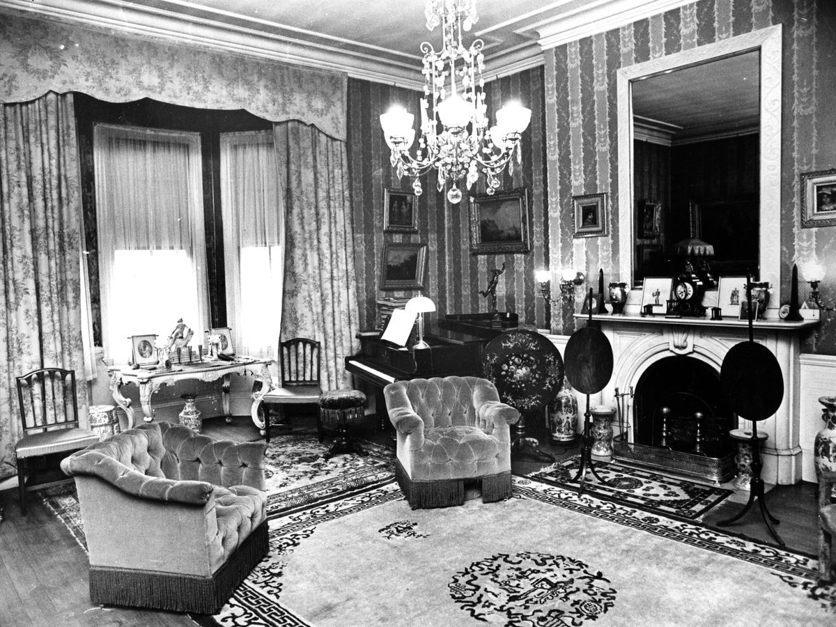 A shot of a 19th-century drawing room with a fireplace and plush furniture.