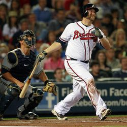 Atlanta Braves' Brian McCann, right, hits a three-run home run as Milwaukee Brewers catcher George Kottaras, left, ooks on in the fifth inning of a baseball game in Atlanta, Friday, April 13, 2012.