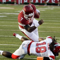 Arkansas running back Knile Davis (7) is tripped up by Jacksonville State defensive back Robert Gray (18) during the first quarter of an NCAA college football game in Fayetteville, Ark., Saturday, Sept. 1, 2012.