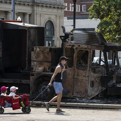 A man and children walk past a truck that was burned in downtown Kenosha during unrest overnight after police shot a Black man, Jacob Blake, in the the 2800 block of 40th Street, Monday morning, Aug. 24, 2020.