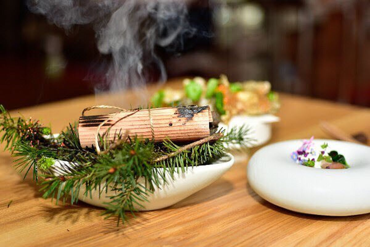 A white bowl of pine needles next to another dish at Birdsong