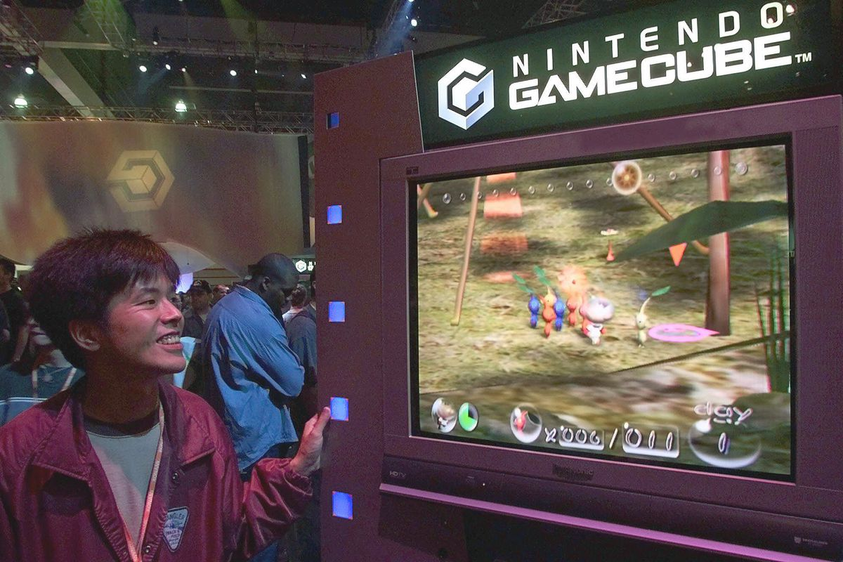 """Tsutomu Hagiwara, director of Genki Co. Ltd., looks at Nintendo's new game """"Pikmin,"""" played on the new Nintendo GameCube console, at the Nintendo of America Inc. booth at the Electronic Entertainment Expo E3, the world's largest video game trade show, Friday, May 18, 2001, at the Los Angeles Convention Center."""