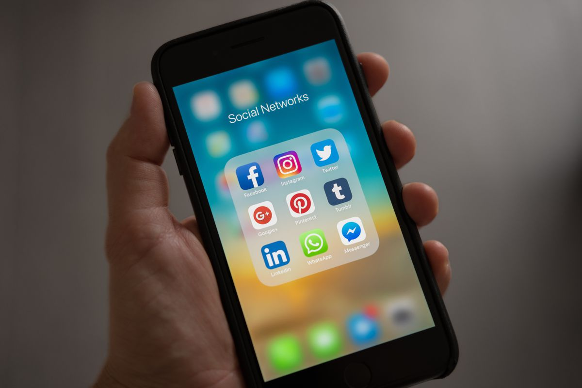 Person holding phone with social media apps