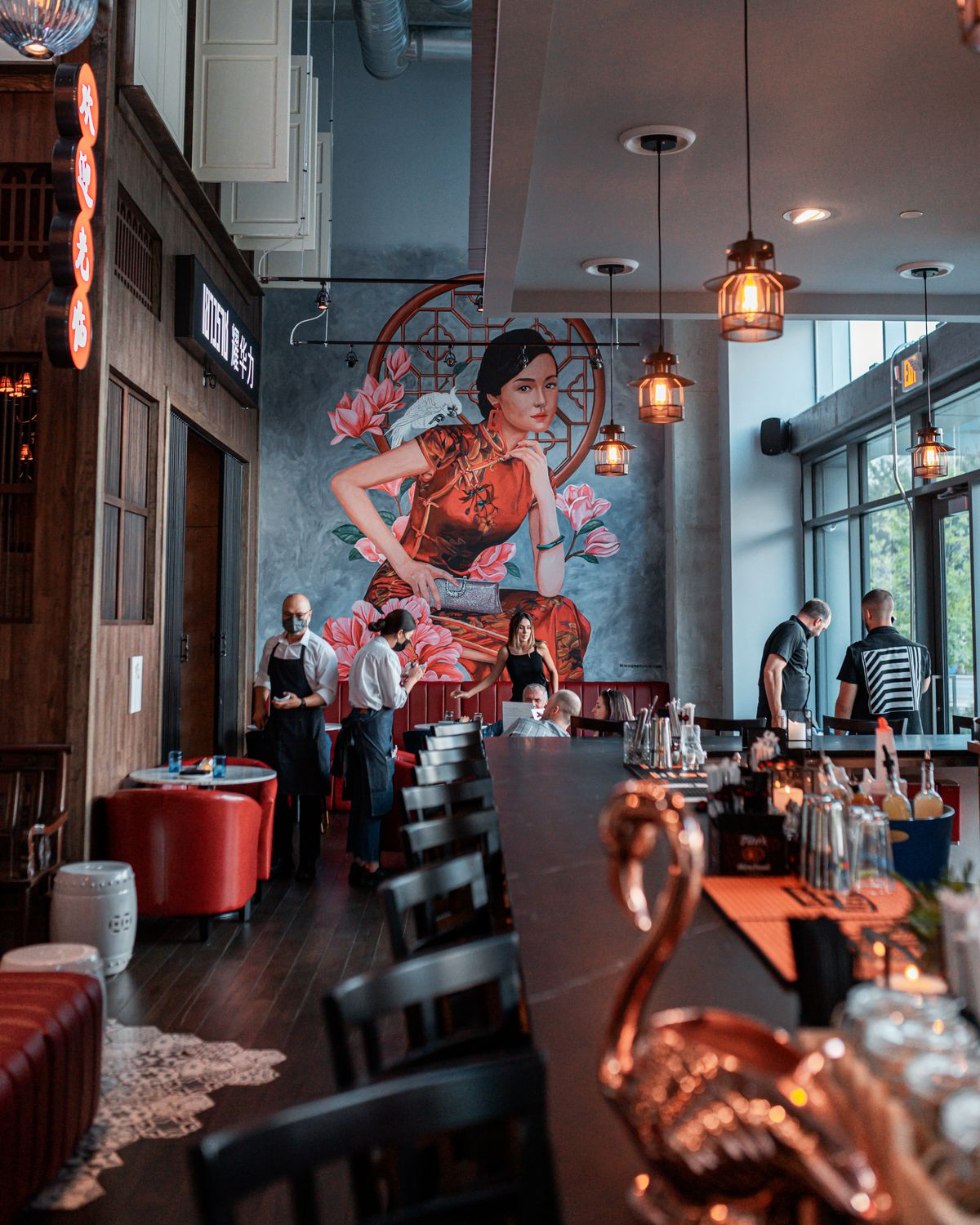 A mural of a woman representing the Chinese community of Bangkok punctuates the bar area at Yao in Dunwoody, GA.