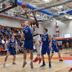 Curie's DaJuan Gordon (3)  puts up a shot over New Trier's Ciaran Brayboy (21), Friday 12-28-18. Worsom Robinson/For Sun-Times