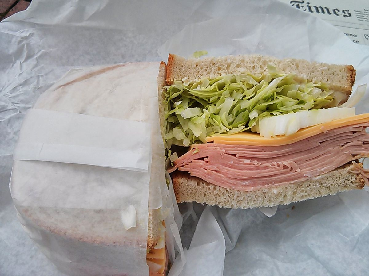 A sandwich with cut side revealing big stack of bologna, lettuce, white onions, and two slices of yellow American cheese.