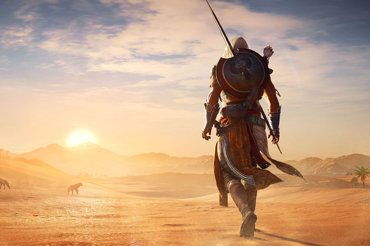 Assassin's Creed Origins - Bayek standing in the desert as the sun rises over sand dunes in the background