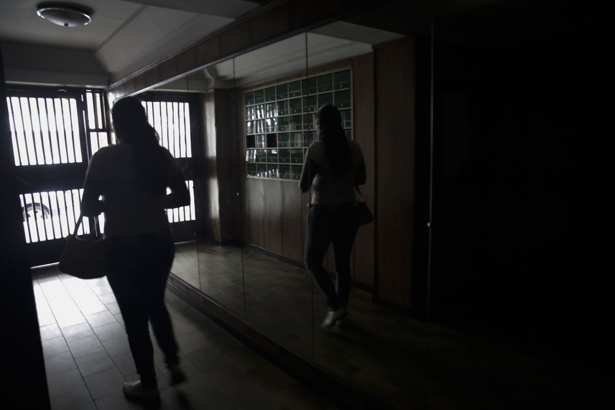 A woman walks out from a building during a power outage on March 25, 2019 in Caracas, Venezuela.