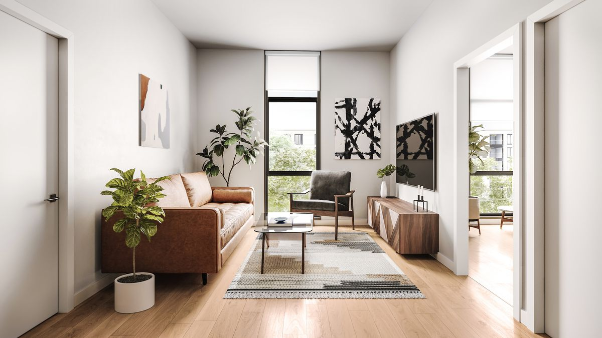 In the living room, there's white walls and hardwood floors. There's a brown leather couch across from a flat screen TV hanging on a wall. There's also a small glass coffee table on a rug and some potted plants.