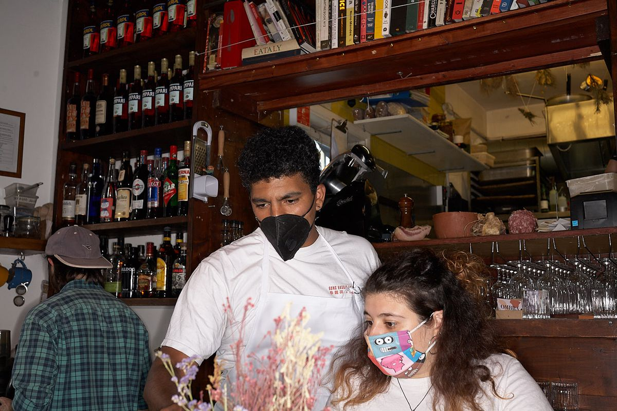 Two restaurant staff wear masks at Ombra in London