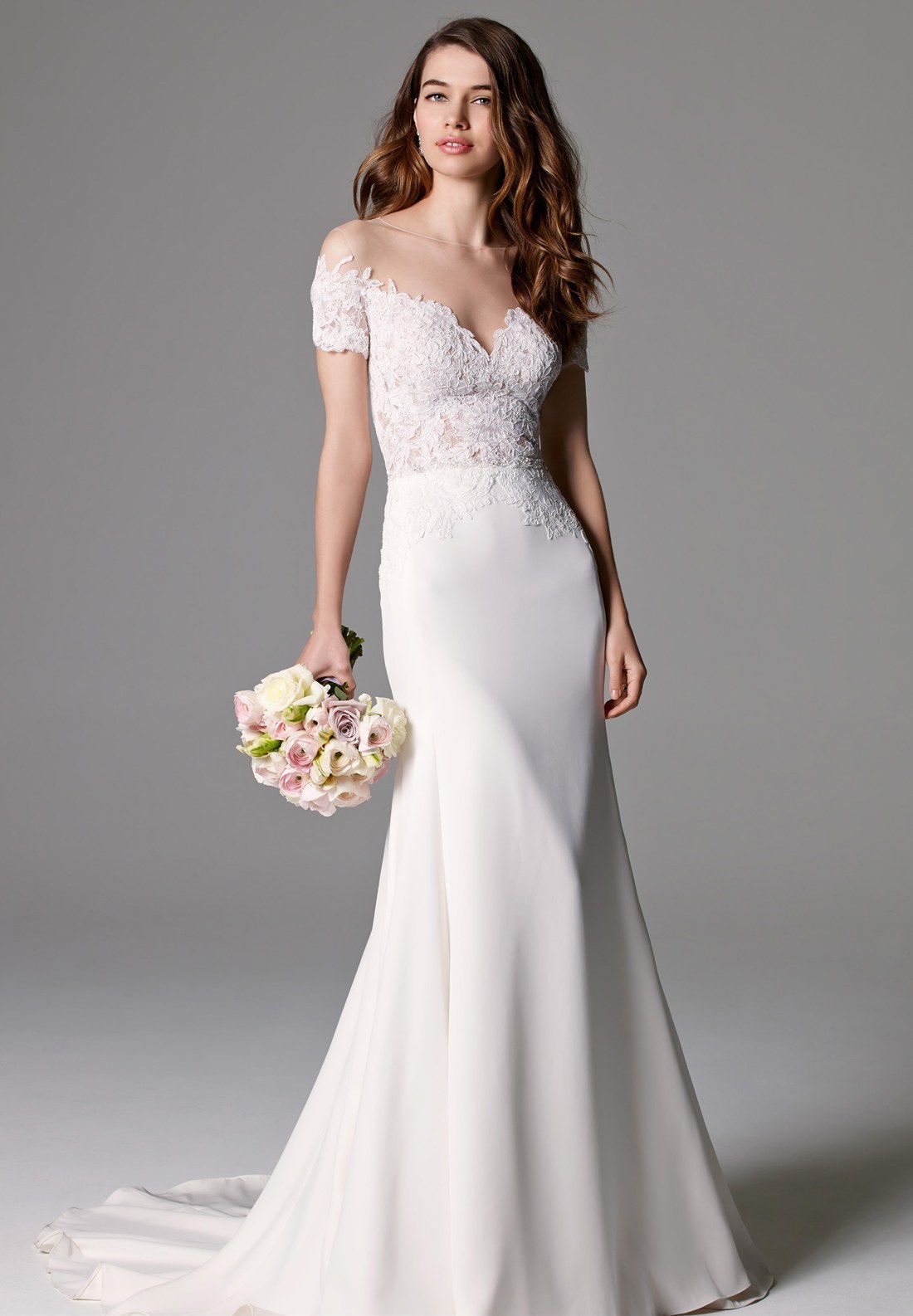 A model in an off-the-shoulder lace wedding gown
