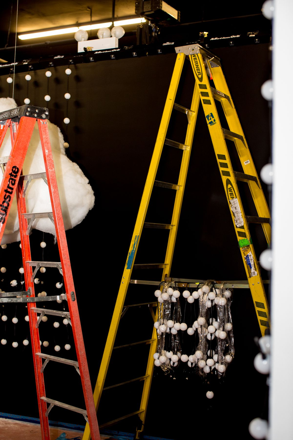 Dream Machine ladders with lights hanging on them, midway through installation or floating clouds/blinking lights room