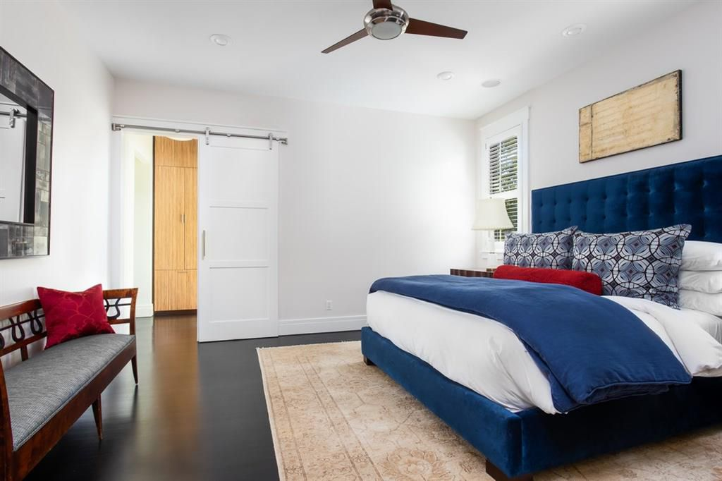 A simple bedroom with wood floors, a barn door, and a large window with a slatted shade. There's a rug on the floor and a bed with and upholstered frame against one wall and a large mirror and bench with a curved back against the opposite wall.