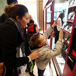 Brittany Ryan helps her son Hudson at one of the Light the World charity vending machines in the Joseph Smith Memorial Building in Salt Lake City on Friday, Dec. 15, 2017.