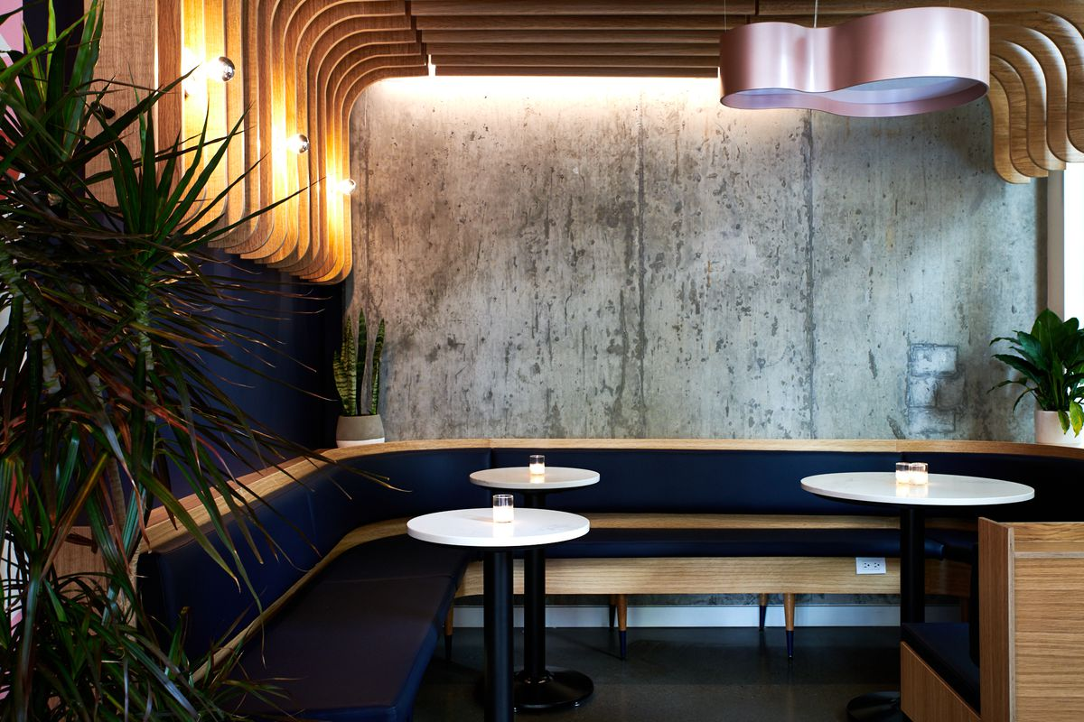 A picture of the lounge space at Bar Diane, with a wooden banquette, white circular tables, and various plants